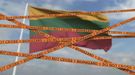 border crossing : Biohazard restriction tape lines against the Lithuanian flag. Restricted border crossing or quarantine in Lithuania. Conceptual looping 3D animation Stock Footage