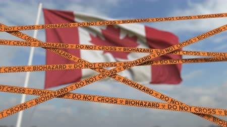 tilalom : Biohazard restriction tape lines against the Canadian flag. Restricted entry or quarantine in Canada. Conceptual looping 3D animation Stock mozgókép