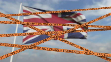 korlátozás : Caution biohazard tape with flag of the UK as a background. British restricted entry or quarantine. Conceptual looping 3D animation