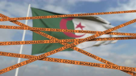 korlátozás : Caution biohazard tape with flag of Algeria as a background. Algerian restricted entry or quarantine. Conceptual looping 3D animation