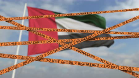 border crossing : Biohazard restriction tape lines against the UAE flag. Restricted border crossing or quarantine. Conceptual looping 3D animation Stock Footage