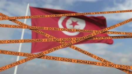 border crossing : Biohazard restriction tape lines against the Tunisian flag. Restricted border crossing or quarantine in Tunisia. Conceptual looping 3D animation