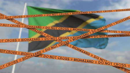 border crossing : Biohazard restriction tape lines against the Tanzanian flag. Restricted border crossing or quarantine in Tanzania. Conceptual looping 3D animation