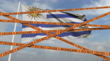 しない : Biohazard restriction tape lines against the Uruguayan flag. Restricted entry or quarantine in Uruguay. Conceptual looping 3D animation 動画素材