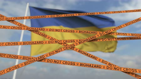 korlátozás : Caution biohazard tape with flag of Ukraine as a background. Ukrainian restricted border crossing or quarantine. Conceptual looping 3D animation Stock mozgókép