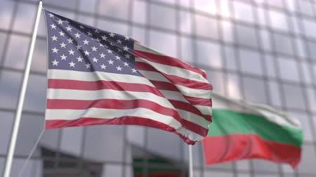 ассоциация : Waving flags of the United States and Bulgaria in front of a modern skyscraper facade