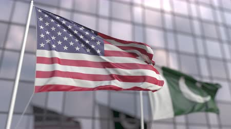 ассоциация : Waving flags of the USA and Pakistan near modern skyscraper