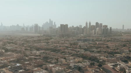 резидент : Aerial dolly zoom shot of Dubais skyline behind residential area, UAE
