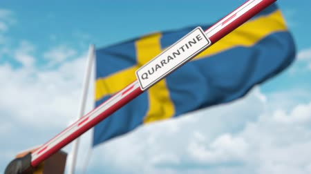 İsveççe : Closing boom barrier with QUARANTINE sign against the Swedish flag. Restricted border crossing or infection related isolation in Sweden