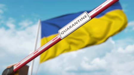 regulamin : Barrier gate with QUARANTINE sign being closed with flag of Ukraine as a background. Ukrainian restricted border crossing or infection related isolation