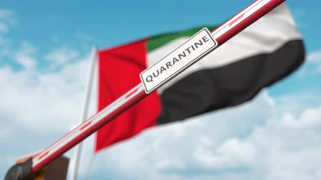 border crossing : Closing boom barrier with QUARANTINE sign against the UAE flag. Restricted border crossing or infection related isolation