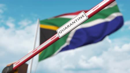 border crossing : Barrier gate with QUARANTINE sign being closed with flag of South Africa as a background. South African restricted border crossing or infection related isolation
