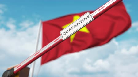 regulamin : Closing boom barrier with QUARANTINE sign against the Vietnamese flag. Border closure or infection related isolation in Vietnam