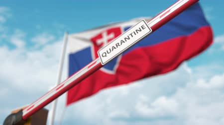 barrier gate : Closing boom barrier with QUARANTINE sign against the Slovak flag. Restricted border crossing or infection related isolation in Slovakia Stock Footage