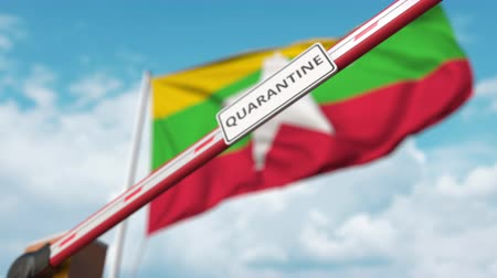 border crossing : Closing boom barrier with QUARANTINE sign against the Myanma flag. Restricted border crossing or infection related isolation in Myanmar Stock Footage