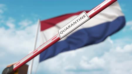 barriers : Closing boom barrier with QUARANTINE sign against the Dutch flag. Restricted border crossing or infection related isolation in Netherlands