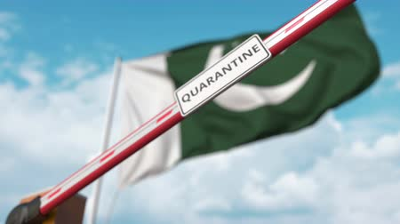 barriers : Barrier gate with QUARANTINE sign being closed with flag of Pakistan as a background. Pakistani Border closure or infection related isolation Stock Footage