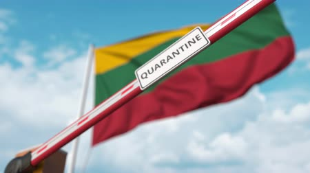 border crossing : Closing boom barrier with QUARANTINE sign against the Lithuanian flag. Restricted border crossing or infection related isolation in Lithuania Stock Footage