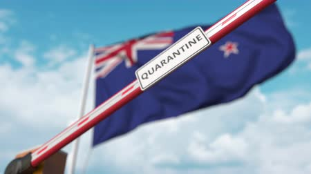 border crossing : Closing boom barrier with QUARANTINE sign against the New zealand flag. Restricted border crossing or infection related isolation in New zealand Stock Footage