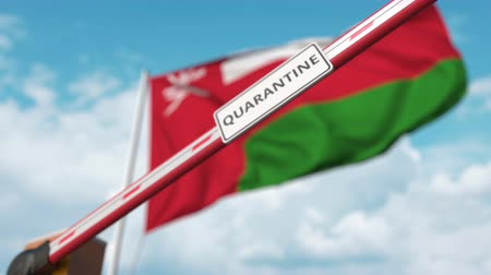epidemy : Closing boom barrier with QUARANTINE sign against the Omani flag. Border closure or infection related isolation in Oman