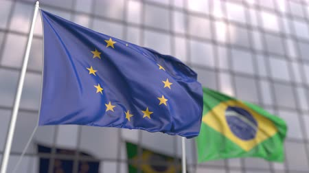 brezilya : Waving flags of the EU and Brazil in front of a modern skyscraper Stok Video
