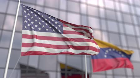 official : Flying flags of the USA and Venezuela in front of a modern skyscraper