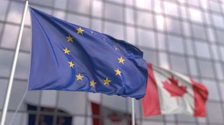 meeting negotiate : Flying flags of the Eropean Union and Canada in front of a modern skyscraper Stock Footage
