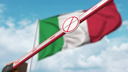 вред : Closing boom barrier with STOP CORONAVIRUS sign against the Italian flag. Quarantine in Italy