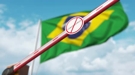 brezilya : Closed boom gate with STOP CORONAVIRUS sign on the Brazilian flag background. Quarantine in Brazil Stok Video
