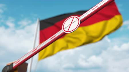bariéra : Closing boom barrier with STOP CORONAVIRUS sign against the German flag. Quarantine in Germany