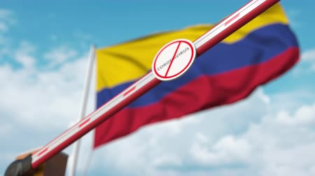 zákaz : Closed boom gate with STOP CORONAVIRUS sign on the Colombian flag background. Quarantine in Colombia