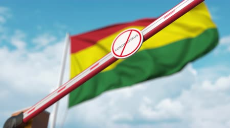 barrier gate : Closing boom barrier with STOP CORONAVIRUS sign against the Bolivian flag. Quarantine in Bolivia Stock Footage