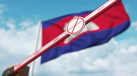 zákaz : Closing boom barrier with STOP CORONAVIRUS sign against the Cambodian flag. Quarantine in Cambodia