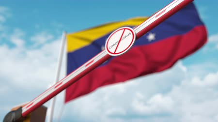 barrier gate : Closing boom barrier with STOP CORONAVIRUS sign against the Venezuelan flag. Quarantine in Venezuela