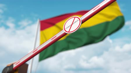 zákaz : Closing boom barrier with STOP CORONAVIRUS sign against the Ghanaian flag. Quarantine in Ghana