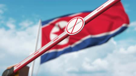 zákaz : Closed boom gate with STOP CORONAVIRUS sign on the North Korean flag background. Quarantine in North Korea
