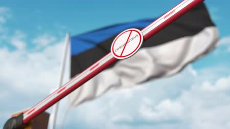 zakaz : Closing boom barrier with STOP CORONAVIRUS sign against the Estonian flag. Quarantine in Estonia Wideo