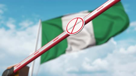 nigeria flag : Closing boom barrier with STOP CORONAVIRUS sign against the Nigerian flag. Quarantine in Nigeria