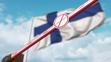 fince : Closing boom barrier with STOP CORONAVIRUS sign against the Finnish flag. Quarantine in Finland Stok Video