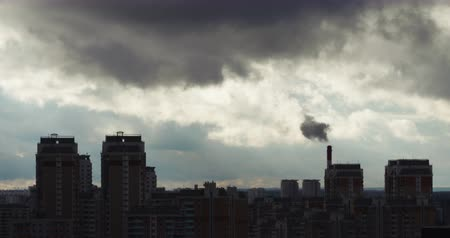 aquecimento global : Red camera telephoto lens time lapse of curling clouds and polluting smoking stack above urban residential area silhouette
