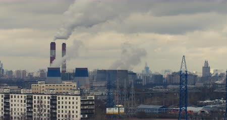 bad ecology : Red camera telephoto lens time lapse of curling clouds and smoking stacks of a depressive industrial urban area. Moscow, Russia