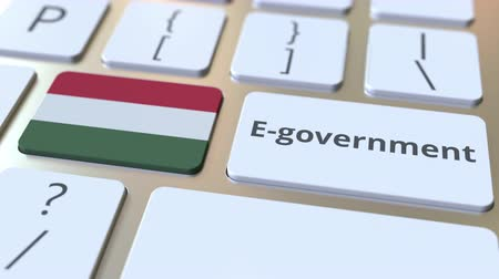 involvement : E-government or Electronic Government text and flag of Hungary on the keyboard. Modern public services related conceptual 3D animation Stock Footage