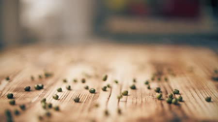 scatters : Green lentils scatter on wooden table, slow motion close-up shot