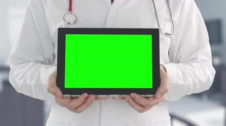 telemedicine : Doctor holds modern tablet with green screen, shot on Red camera. Alpha matte for easy picture or video placement Stock Footage