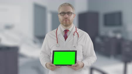 betrokken : Concerned doctor holds modern tablet PC with green screen, shot on Red camera. Alpha matte for easy picture or video placement