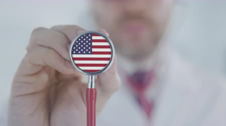 diagnóstico : Doctor holds stethoscope bell with the American flag. Healthcare in the USA