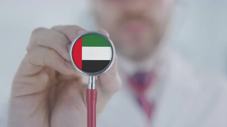 diagnóstico : Doctor holds stethoscope bell with the UAE flag. Healthcare in the United Arab Emirates