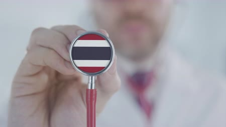 diagnóstico : Doctor holds stethoscope bell with the Thai flag. Healthcare in Thailand Stock Footage