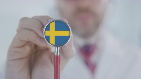 diagnóstico : Medical doctor holds stethoscope bell with the Swedish flag. Healthcare in Sweden