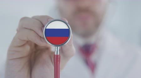 diagnóstico : Doctor listening with the stethoscope with flag of Russia. Russian healthcare